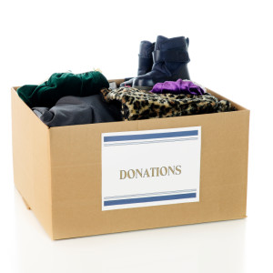 "A large corrugated box with a ""Donations"" sign and filled with an assortment of warm, winter clothing. On a white background."